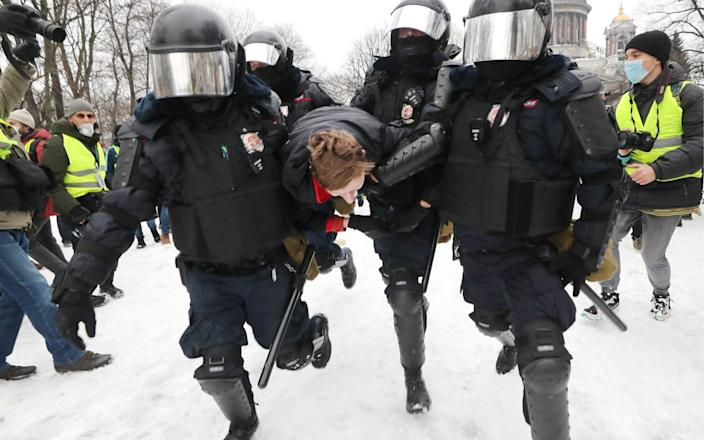 Riot police officers detain a participant in an unauthorized rally in support of Russian opposition activist Alexei Navalny in St. Petersburg - Alexander Demianchuk /TASS