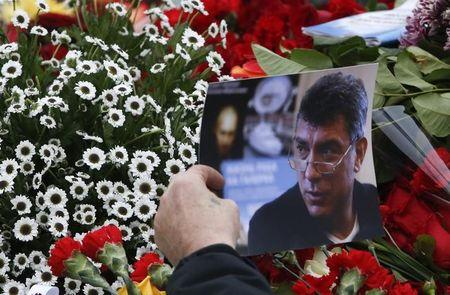 A visitor holds a photo at the site where Boris Nemtsov was recently murdered, in central Moscow, February 28, 2015. REUTERS/Sergei Karpukhin