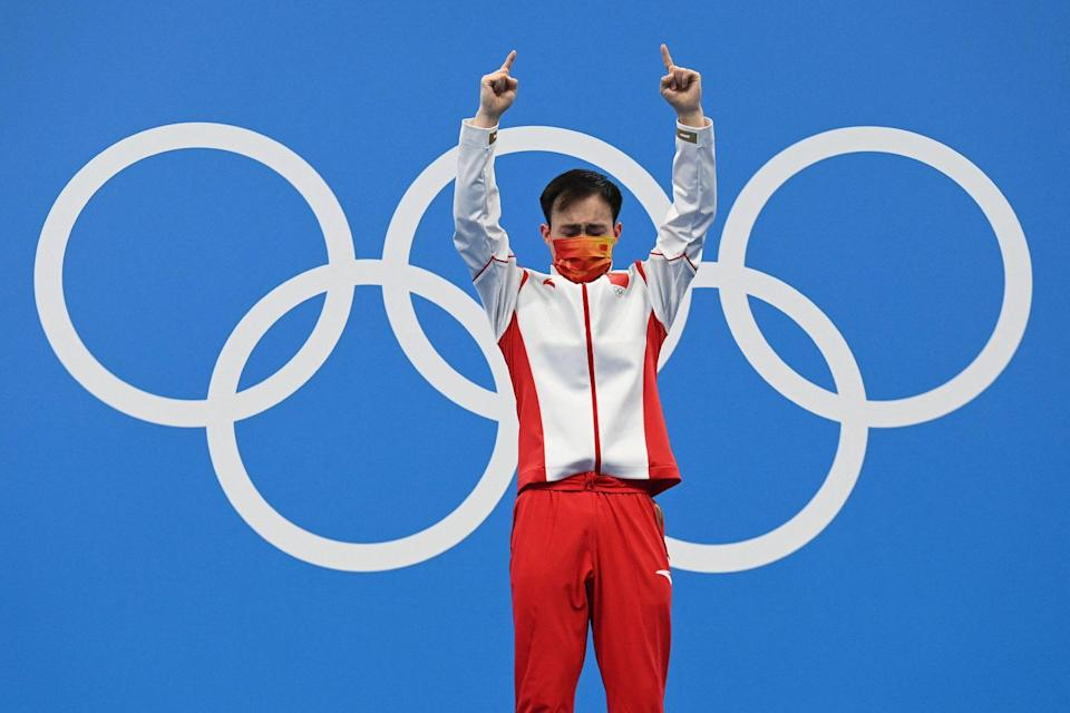 <p>Gold medallist China's Xie Siyi points to the sky as he steps up to the podium after winning the men's 3m springboard diving final at the Tokyo Aquatics Centre on August 3.</p>