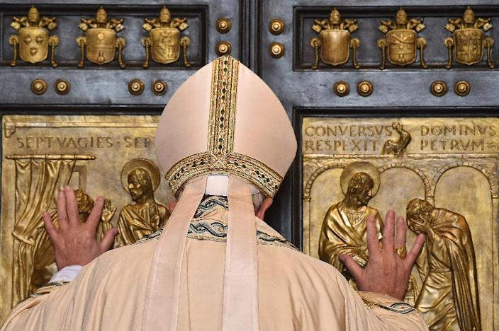 """Pope Francis opens a """"Holy Door"""" at St Peter's basilica to mark the start of the Jubilee Year of Mercy at the Vatican, on December 8, 2015 (AFP Photo/Vincenzo Pinto)"""