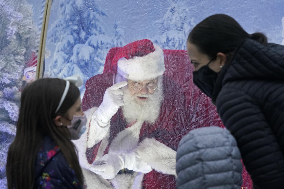 """Santa, portrayed by Dan Kemmis, talks to a family wearing masks as he sits inside a protective bubble in Seattle's Greenwood neighborhood on Dec. 8, 2020. Kemmis has been Santa in past years, but he started his daily appearances early this year and added his """"snow globe"""" tent due to the Coronavirus pandemic. In this socially distant holiday season, Santa Claus is still coming to towns (and shopping malls) across America but with a few 2020 rules in effect. (AP Photo/Ted S. Warren)"""