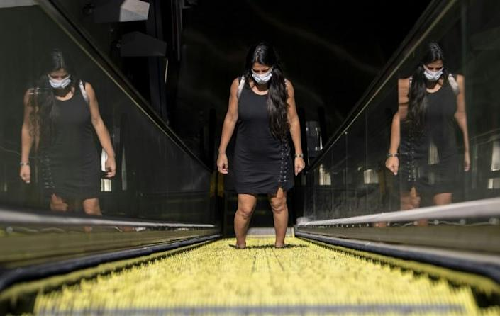 A commuter wears a face mask as she leaves a subway station in Santiago, Chile (AFP Photo/MARTIN BERNETTI)