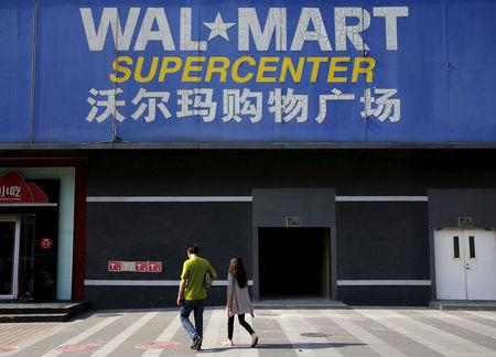 FILE PHOTO: Pedestrians walk past a signboard of Wal-Mart at its branch store in Beijing, China