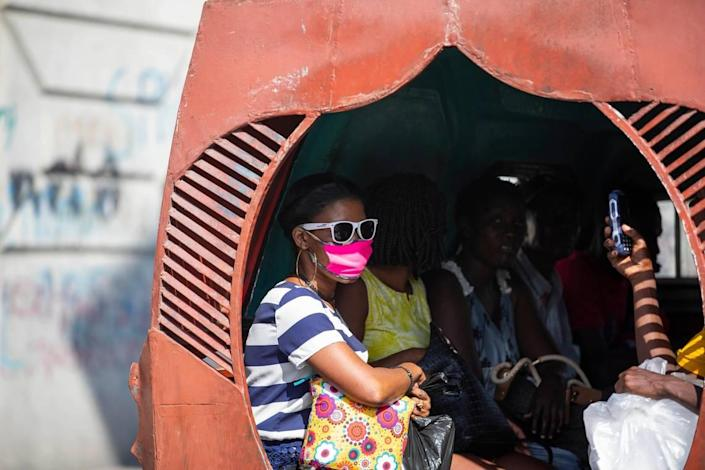 People sit in a Tap-tap while a passenger wears a mask to protect herself from the spread of the new coronavirus in Port-au-Prince, Haiti. Fear of insecurity has ridership on public buses down, transport unions say.