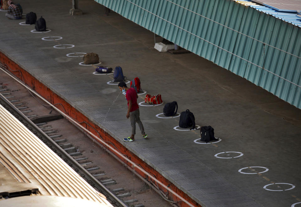 A man spits water on rail tracks as passengers line up their bags on the railway station platform to reserve their spots in boarding queue in New Delhi, India, Tuesday, May 12, 2020. India is reopening some of its colossal rail network as the country looks at easing its nearly seven-week strict lockdown amid an increase in coronavirus infections. (AP Photo/Manish Swarup)
