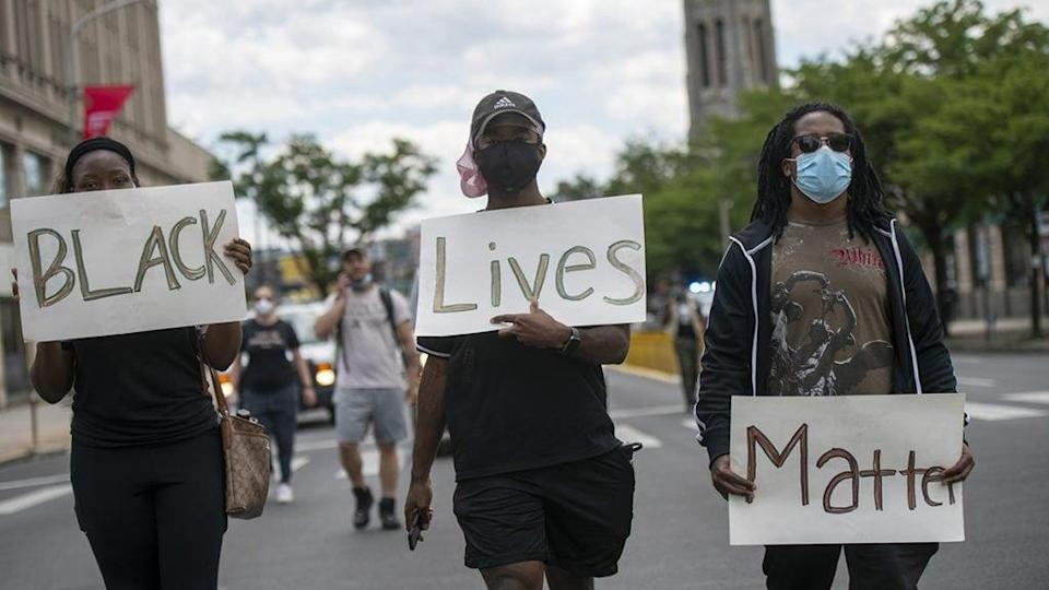 """Protesters march with three placards stating """"Black Lives Matter"""" in the aftermath of widespread unrest following the death of George Floyd on June 1, 2020 in Philadelphia, Pennsylvania. (Photo by Mark Makela/Getty Images)"""