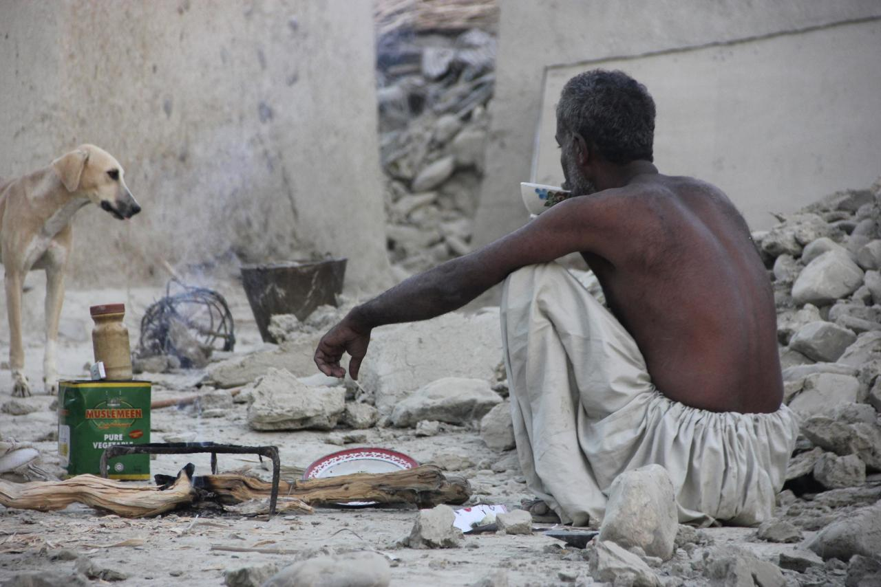 A survivor of an earthquake sits as he takes tea on the rubble of a mud house after it collapsed following the quake in the town of Awaran, southwestern Pakistani province of Baluchistan, September 25, 2013. The death toll from a powerful earthquake in Pakistan rose to at least 208 on Wednesday after hundreds of mud houses collapsed on people in a remote area near the Iranian border, officials said. REUTERS/Sallah Jan (PAKISTAN - Tags: DISASTER)