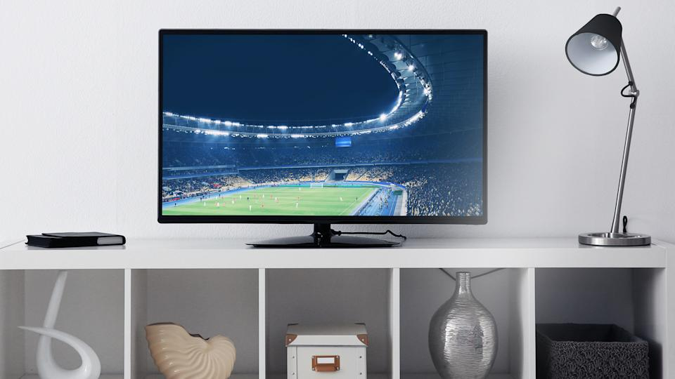 television monitor next to lamp on top of bookshelf