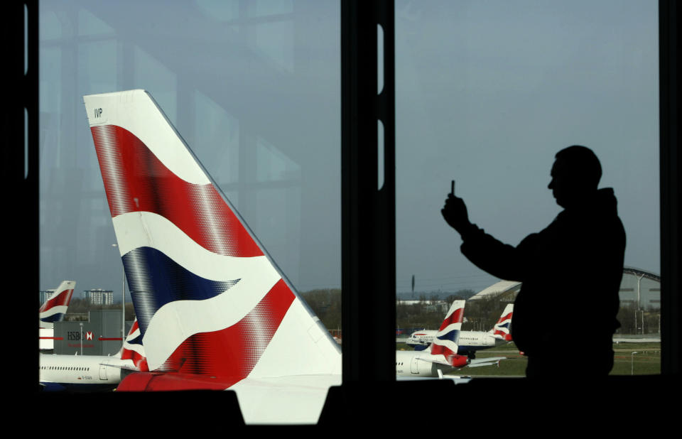 A passenger is seen photographing a British Airways aircraft with his mobile telephone at Heathrow Airport near London in this March 15, 2009 file photo. British Airways slumped to a record loss, nearly doubled its debt pile and cancelled its dividend, adding the tough conditions made it impossible to give any guidance for the current period.  Europe's third-biggest airline by revenue posted operating losses of 220 million pounds ($347.5 million) on May 22, 2009, compared to a profit of 875 million pounds in 2007/08.      REUTERS/Luke MacGregor/    (BRITAIN TRANSPORT BUSINESS TRAVEL)
