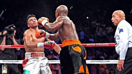 Victor Ortiz (L) falls towards the canvas after being hit with a right from Floyd Mayweather