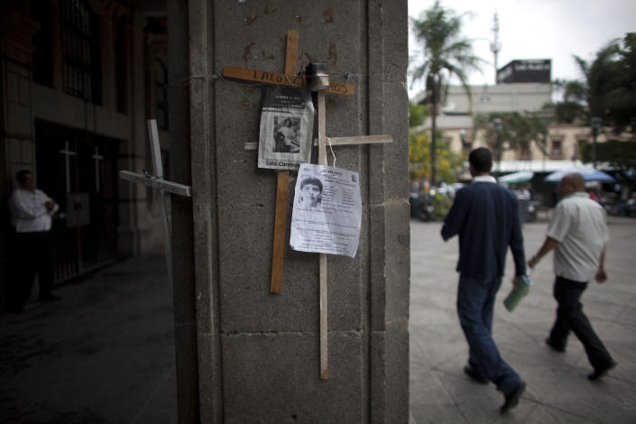 In this photo taken on Thursday, June 21, 2012, two men walk past posters of missing people attached to crosses hanging from a pillar of the governor's palace in the main square of Cuernavaca, Mexico. As Mexicans head to the ballot box Sunday, drug cartels are registering their votes with scare tactics and cold, hard cash to make sure whoever is elected doesn't interfere with their lucrative operations. (AP Photo/Alexandre Meneghini)