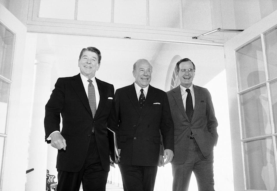 FILE - In this Jan. 9, 1985 file photo, Secretary of State George Shultz, center, walks with President Ronald Reagan and Vice President George Bush upon his arrival at the White House in Washington, after two days of arms talks with the Soviet Union in Geneva. Shultz, former President Reagan's longtime secretary of state, who spent most of the 1980s trying to improve relations with the Soviet Union and forging a course for peace in the Middle East, died Saturday, Feb. 6, 2021. He was 100. (AP Photo/Barry Thumma, File)