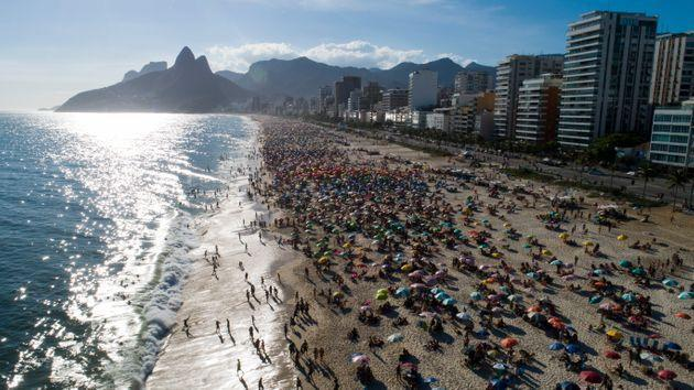 Beachgoers crowd Ipanema beach in Brazil. The country remains on the