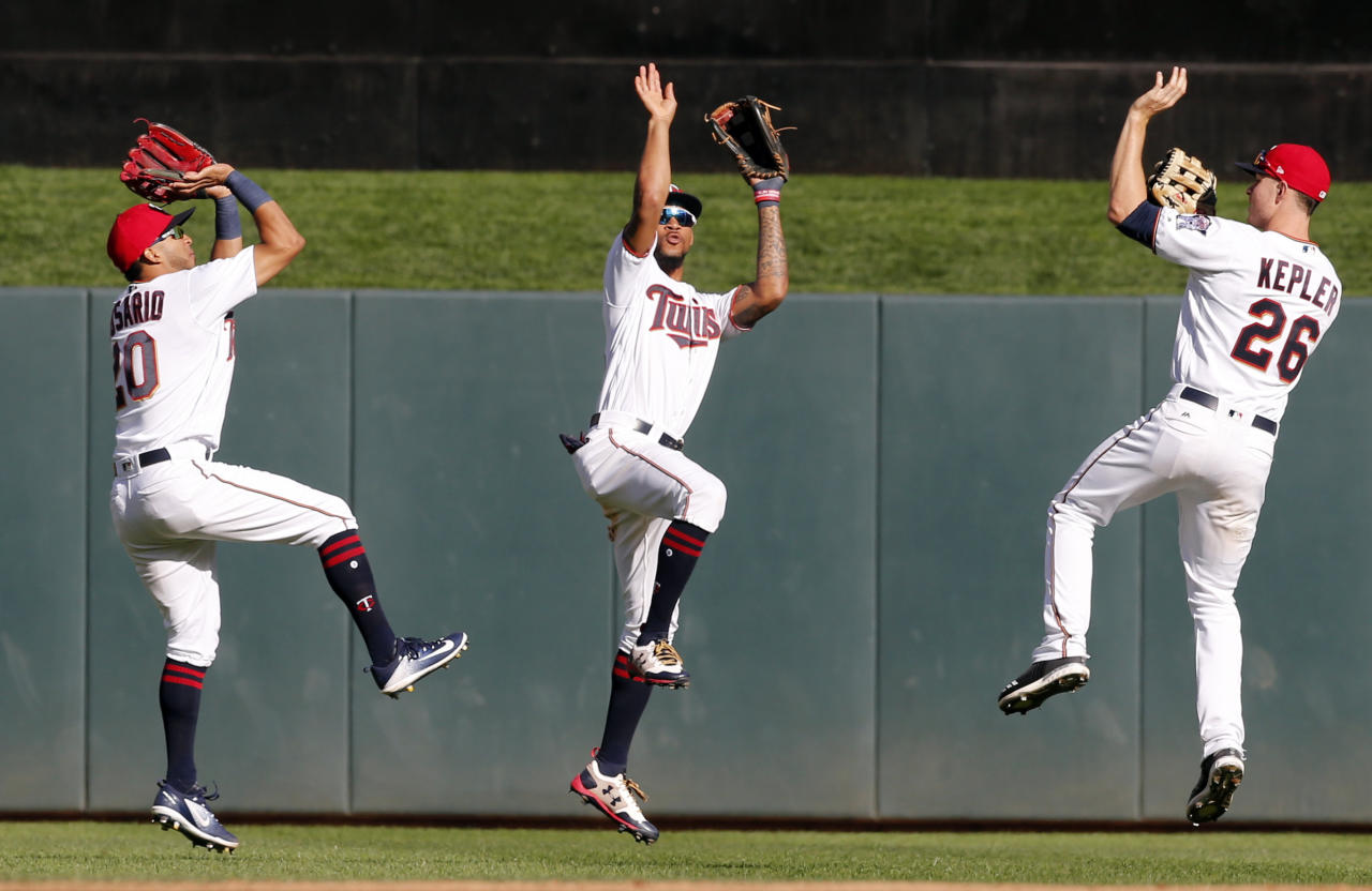 Minnesota Twins outfielders Eddie Rosario, left, Byron Buxton and Max Kepler, right, show their basketball three-point form after the Twins beat the Toronto Blue Jays 13-7 in a baseball game Sunday, Sept. 17, 2017, in Minneapolis. Rosario hit two home runs in the game. (AP Photo/Jim Mone)