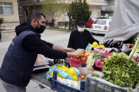 A street vendor wearing a mask to help protect against the spread of coronavirus, serves a client hours before a two-day weekend nationwide lockdown, in Ankara, Turkey, Friday, April 16, 2021. Turkey's daily tally of COVID-19 deaths reached a record high of 341 on Monday, April 19, 2021, Health Ministry data showed. The deaths take the official toll to 34,267, in the country which now ranks among the world's worst-hit. (AP Photo/Burhan Ozbilici)