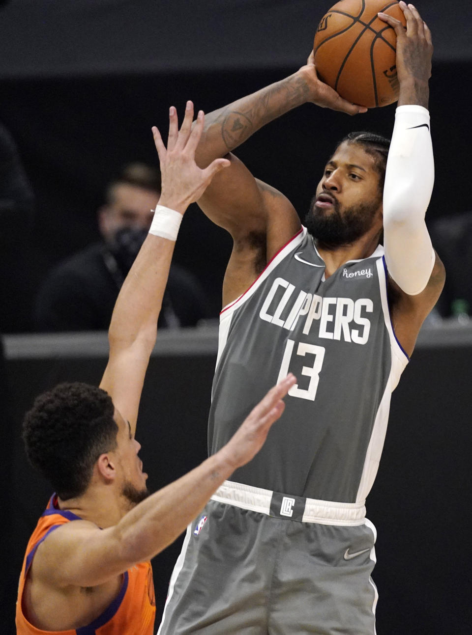 Los Angeles Clippers guard Paul George, right, shoots as Phoenix Suns guard Devin Booker defends during the second half in Game 4 of the NBA basketball Western Conference Finals Saturday, June 26, 2021, in Los Angeles. (AP Photo/Mark J. Terrill)