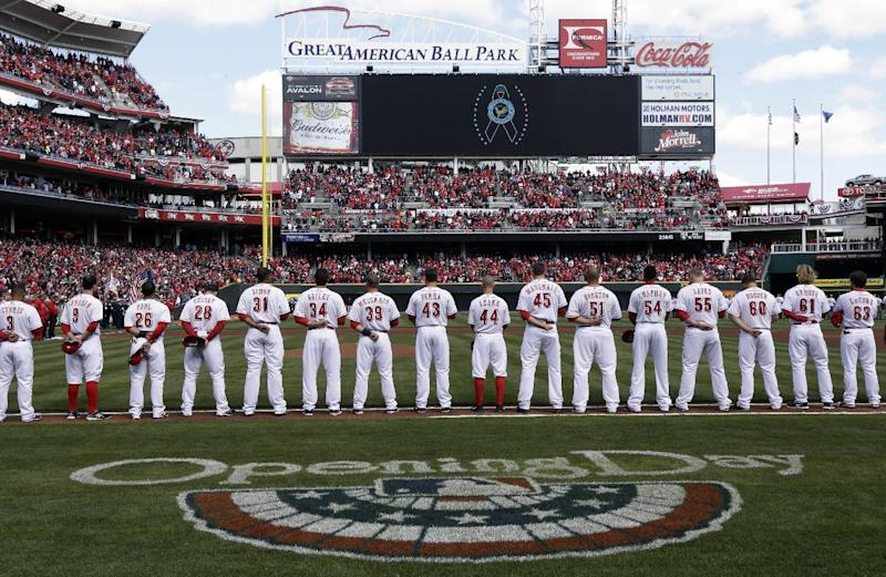 The Cincinnati Reds hang their heads in a moment of silence for the victims of the Sandy Hook Elementary School shooting during introductions before a baseball game against the Los Angeles Angels, Monday, April 1, 2013, in Cincinnati. (AP Photo/Al Behrman)