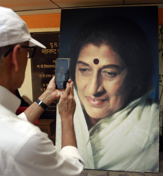 A man takes a photograph of a giant portrait of Indian musician Kishori Amonkar in Mumbai, India, Tuesday, April 4, 2017. Amonkar, renowned for her innovative interpretation of classical Indian music, has died, one of her students said Tuesday. She was 84. (AP Photo/Rafiq Maqbool)