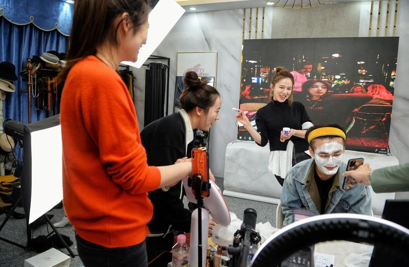 Live-streaming anchor and her assistant promote a facial mask through a live streaming session before the 11.11 Singles' Day shopping festival, at her studio in Hangzhou