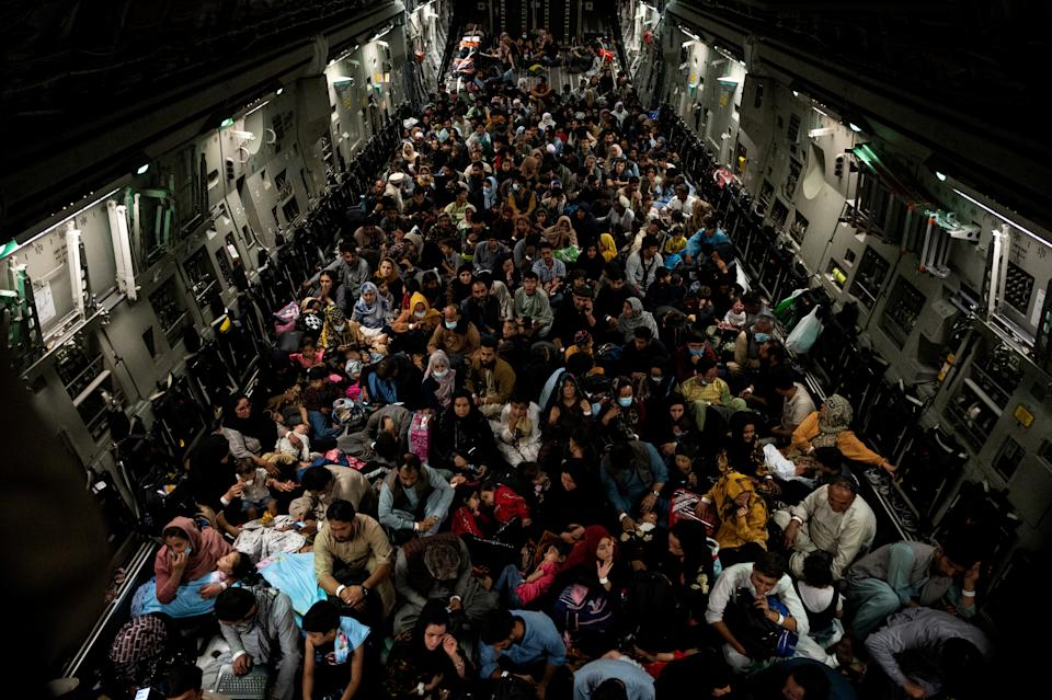 Evacuees from Afghanistan sit inside a military aircraft during an evacuation from Kabul, in this photo taken on August 19, 2021 at undisclosed location and released on August 20, 2021. ( Staff Sgt. Brandon Cribelar/U.S. Marine Corps/Handout via Reuters)