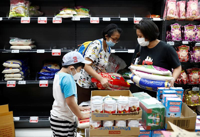 People stock up on rice after Singapore raised the coronavirus outbreak alert level to orange, at a supermarket in Singapore February 8, 2020. REUTERS/Edgar Su