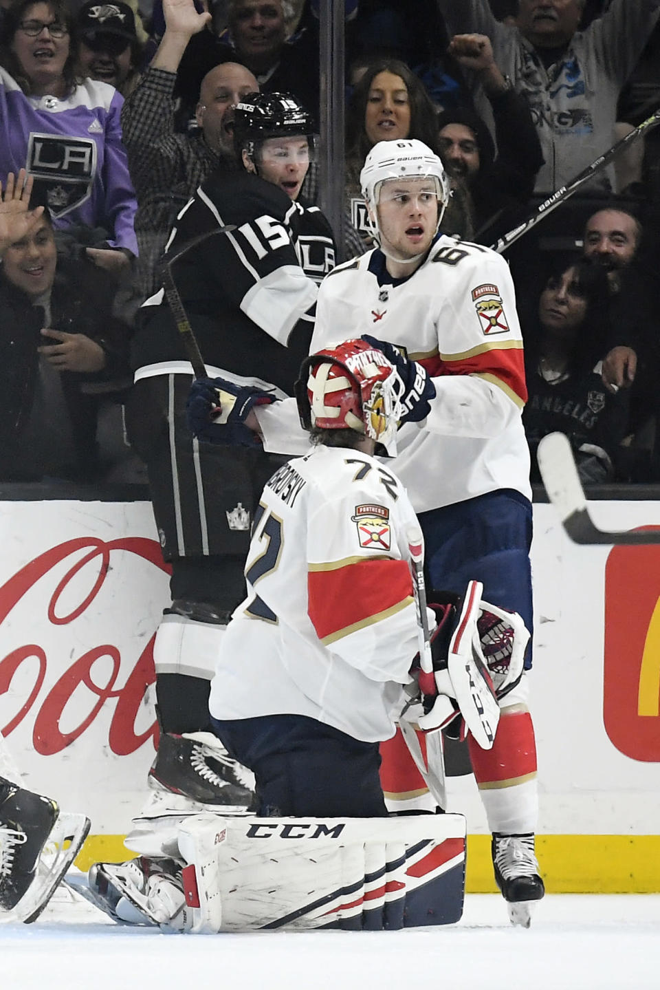 Los Angeles Kings defenseman Ben Hutton, left, celebrates his goal as Florida Panthers goaltender Sergei Bobrovsky, center, kneels on the ice while defenseman Riley Stillman stands by during the third period of an NHL hockey game Thursday, Feb. 20, 2020, in Los Angeles. The Kings won 5-4. (AP Photo/Mark J. Terrill)