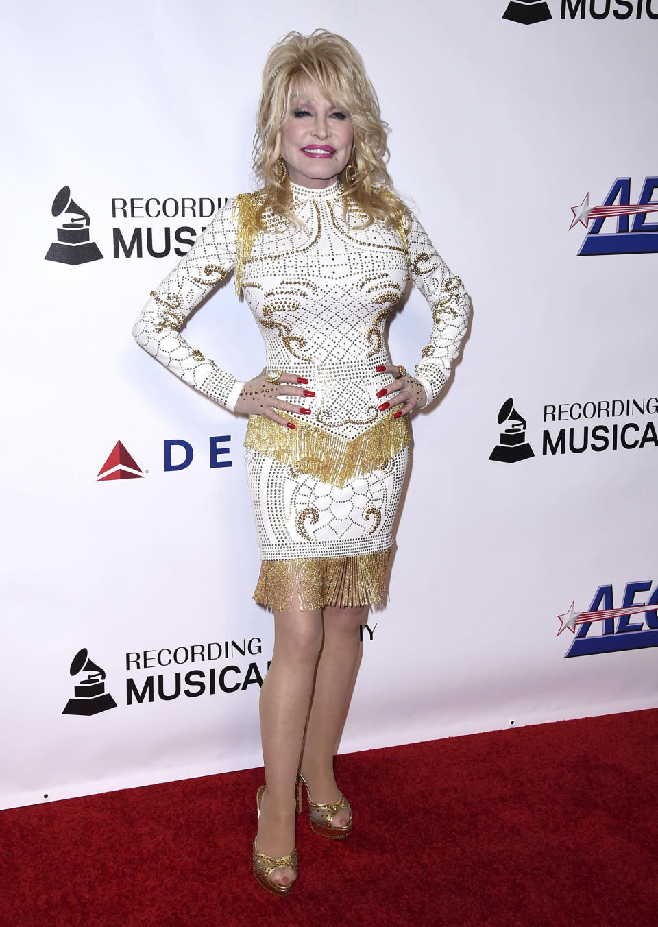 FILE - In this Feb. 8, 2019 file photo, Dolly Parton arrives at MusiCares Person of the Year in her honor at the Los Angeles Convention Center. The white and gold long sleeve dress worn by Parton is among a collection of items that will be sold to benefit the Recording Academy's MusiCares, which helps provide health and other safety net assistance for those who need it in the music industry. The sale, hosted by Julien's Auctions, will be held Jan. 30, 2022, during the runup to the Grammys. (Photo by Jordan Strauss/Invision/AP, File)