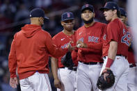 Boston Red Sox starting pitcher Eduardo Rodriguez hands the ball to manager Alex Cora as he is taken out in the fifth inning of the team's baseball game against the Houston Astros at Fenway Park, Thursday, June 10, 2021, in Boston. (AP Photo/Elise Amendola)
