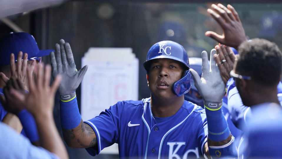 Kansas City Royals' Salvador Perez is congratulated by teammates after hitting a solo home run off Cleveland Indians starting pitcher Shane Bieber in the fourth inning of a baseball game against the Cleveland Indians, Wednesday, April 7, 2021, in Cleveland. (AP Photo/Tony Dejak)
