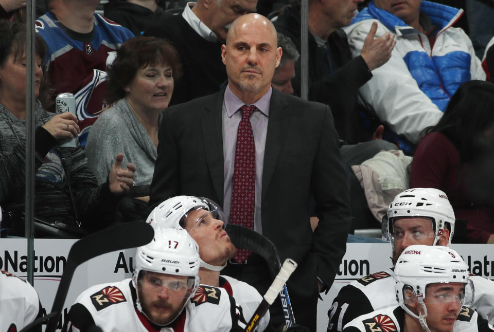 FILE - In this March 29, 2019, file photo, Arizona Coyotes head coach Rick Tocchet, center top, looks on in the second period of an NHL hockey game against the Colorado Avalanche in Denver. The Coyotes and Tocchet have mutually agreed to part ways after four seasons. The announcement Sunday, May 9, 2021, comes a day after the Coyotes missed the playoffs for the seventh time in eight seasons. (AP Photo/David Zalubowski, File)
