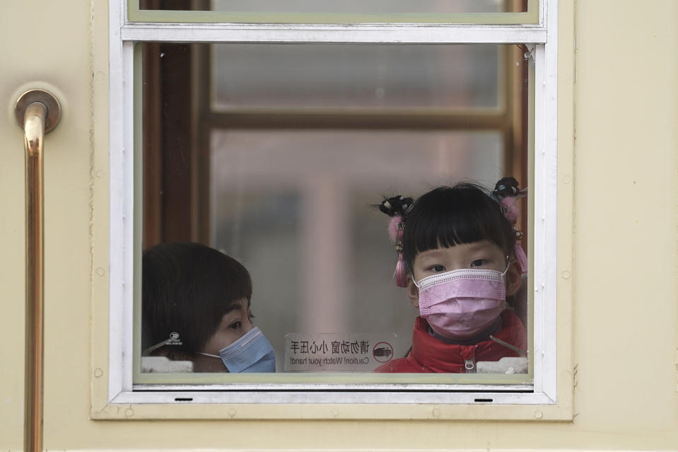 A child and a woman, both wearing face masks to help curb the spread of the coronavirus, ride a train at Qianmen Street, a popular tourist spot in Beijing, Sunday, Jan. 31, 2021. A World Health Organization team looking into the origins of the coronavirus pandemic on Sunday visited the seafood market in the Chinese city of Wuhan that was linked to many early infections. (AP Photo/Andy Wong)