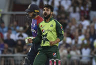 Pakistan's Shadab Khan, right, celebrates the dismissal of England's Jos Buttler, left, during the third Twenty20 international cricket match between England and Pakistan at Old Trafford in Manchester, Tuesday, July 20, 2021. (AP Photo/Rui Vieira)
