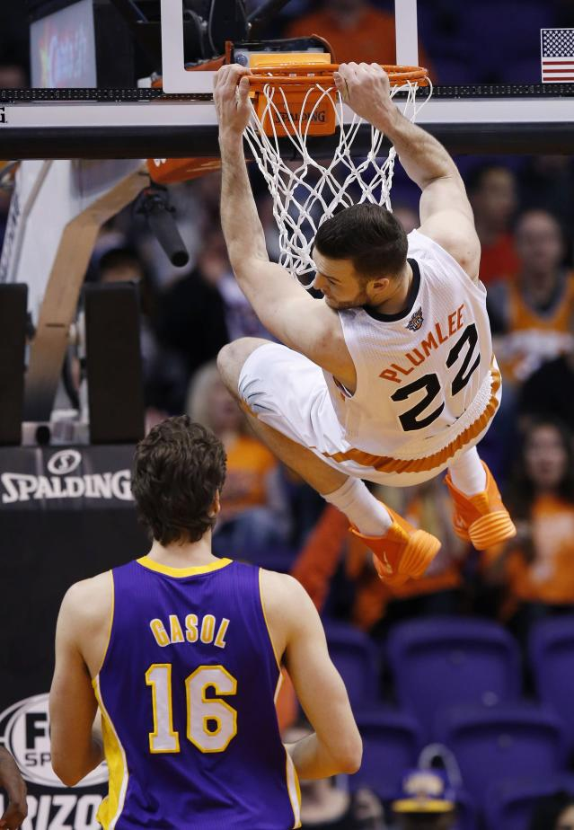 Phoenix Suns' Miles Plumlee (22) hangs from the rim after dunking as Los Angeles Lakers' Pau Gasol (16), of Spain, watches during the first half of an NBA basketball game Wednesday, Jan. 15, 2014, in Phoenix. (AP Photo/Ross D. Franklin)