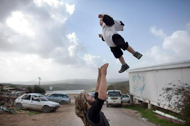 HAVAT GILAD, WEST BANK - FEBRUARY 24: (ISRAEL OUT) A Jewish settler plays with his baby as settlers celebrate the Jewish festival of Purim February 24, 2013 at the settlement outpost of Havat Gilad, West Bank. The carnival-like Purim holiday is celebrated with parades and costume parties to commemorate the deliverance of the Jewish people from a plot to exterminate them in the ancient Persian empire 2,500 years ago, as described in the Book of Esther. (Photo by Uriel Sinai/Getty Images)Ê