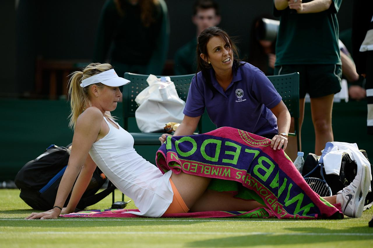 LONDON, ENGLAND - JUNE 26: Maria Sharapova of Russia receives treatment during her Ladies' Singles second round match against Michelle Larcher de Brito of Portugal on day three of the Wimbledon Lawn Tennis Championships at the All England Lawn Tennis and Croquet Club on June 26, 2013 in London, England. (Photo by Dennis Grombkowski/Getty Images)