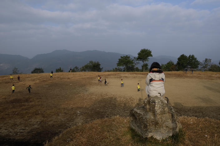 A girl watches a soccer match early morning in Ukhrul, in the northeastern Indian state of Manipur, Saturday, Jan. 16, 2021. This small mountain town escaped the worst of the pandemic, which ravaged most of the country, helped by community efforts to stem the virus. But like elsewhere in the world, life was also upended. India has started inoculating health workers Saturday in what is likely the world's largest COVID-19 vaccination campaign, joining the ranks of wealthier nations where the effort is already well underway. (AP Photo/Yirmiyan Arthur)
