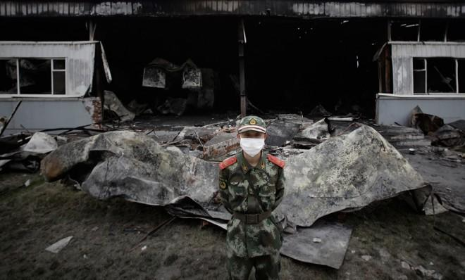 A policeman stands guard outside the burned out poultry slaughterhouse in rural northeast China where 119 workers died, trapped behind bolted doors.