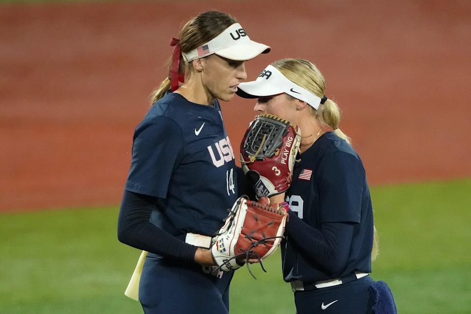 Team United States utility Allyson Carda (3) hands pitcher Monica Abbott (14) the ball and talks during a pitching change against Japan during the fifth inning in the gold medal game of the Tokyo Olympics.