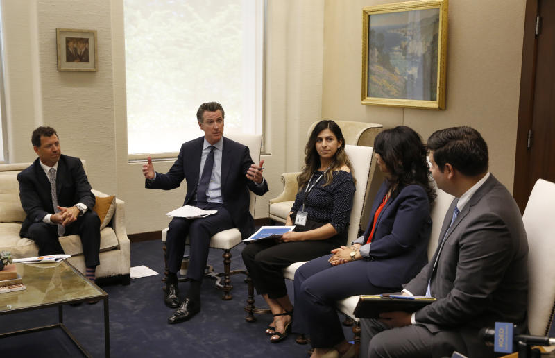 In this photo taken June 4, 2019, Gov. Gavin Newsom meets with a group of small business owners and government officials to discuss tax relief at his Capitol office in Sacramento, Calif. Lawmakers approved the state budget, Thursday, June 13, 2019, that includes an expansion of the state's earned income tax credit. Newsom wants to pay for it by adopting some of President Donald Trump's 2017 tax overhaul, but Assembly Democrats are cautious about this idea. (AP Photo/Rich Pedroncelli)