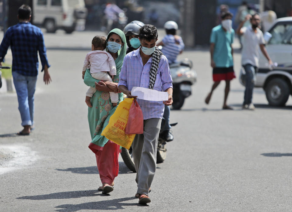 People wearing face masks as a precaution against the coronavirus walk outside a government hospital in Jammu, India, Saturday, Sept. 19, 2020. India's coronavirus cases are now the second-highest in the world and only behind the United States. (AP Photo/Channi Anand)