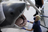 """Phyllis Cottrell, exhibitions installation manager for new Academy of Museum of Motion Pictures, watches over a fiberglass replica of Bruce, the shark featured in Steven Spielberg's 1975 classic """"Jaws,"""" before it was raised into a suspended position for display at the museum, Friday, Nov. 20, 2020, in Los Angeles. The museum celebrating the art and science of movies is scheduled to open on April 30, 2021. (AP Photo/Chris Pizzello)"""