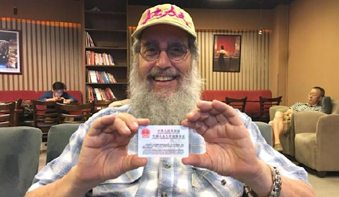 Mark Levine with his foreigner's permanent residence identity card, awarded in the summer of 2017, in Beijing. Photo: Xinhuanet