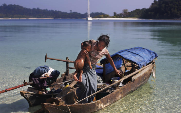 In this Sunday, Feb. 9, 2014 photo, a woman belonging to Moken tribe, nomads of the sea, carries her child as she steps out of her canoe on Island 115 in Mergui Archipelago, Myanmar. Isolated for decades by the country's former military regime and piracy, the Mergui archipelago is thought by scientists to harbor some of the world's most important marine biodiversity and looms as a lodestone for those eager to experience one of Asia's last tourism frontiers before, as many fear, it succumbs to the ravages that have befallen many of the continent's once pristine seascapes. Although no accurate census is available, about 2,000 Moken are believed to inhabit the archipelago, significantly reduced through migration, intermarriage with Burmese and deaths of males from rampant alcohol and drug abuse. (AP Photo/Altaf Qadri)