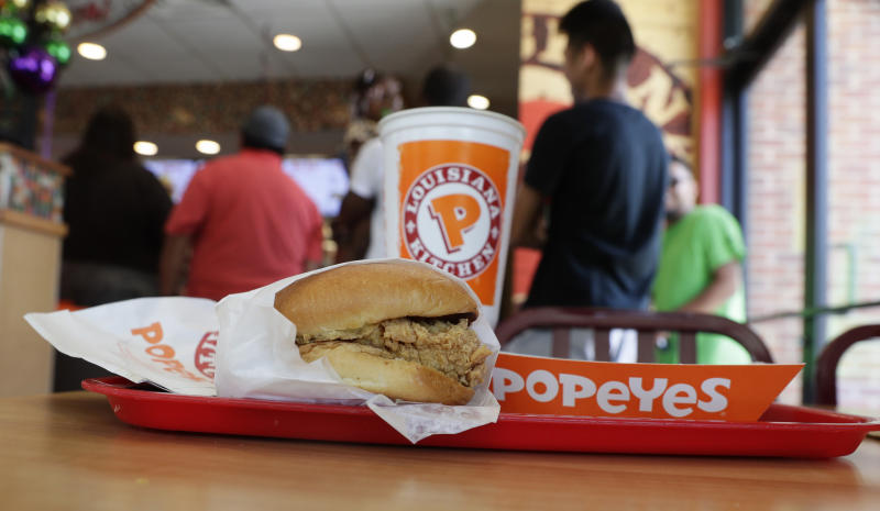 A chicken sandwich sits on a table at a Popeyes as guests wait in line, Thursday, Aug. 22, 2019, in Kyle, Texas. After Popeyes added a crispy chicken sandwich to their fast-fast menu, the hierarchy of chicken sandwiches in America was rattled, and the supremacy of Chick-fil-A and others was threatened. It's been a trending topic on social media, fans have weighed in with YouTube analyses and memes, and some have reported long lines just to get a taste of the new sandwich. (AP Photo/Eric Gay)