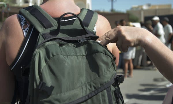 Thief removing item from tourist's backpack, rear view, close-up of hand