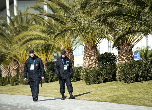 Russian police officers walk past a row of palm trees while taking in the sunny mild temperatures before the 2014 Sochi Winter Olympics in Sochi, Russia on Tuesday, Feb. 4, 2014. (AP Photo/The Canadian Press, Nathan Denette)