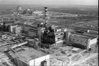 FILE - This April 26, 1986 file photo shows an aerial view of the Ukrainian Chernobyl nuclear plant, with damage from an explosion and fire in reactor four on that sent large amounts of radioactive material into the atmosphere. The vast and empty Chernobyl Exclusion Zone around the site of the world's worst nuclear accident is a baleful monument to human mistakes. Yet 35 years after a power plant reactor exploded, Ukrainians also look to it for inspiration, solace and income. (AP Photo/ Volodymyr Repik)