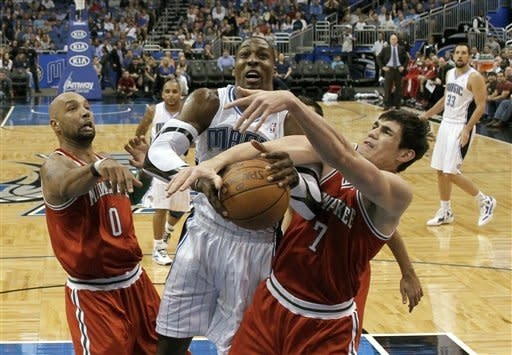 Milwaukee Bucks' Drew Gooden (0) and Ersan Ilyasova (7) battle with Orlando Magic's Dwight Howard, center, for a rebound during the first half of an NBA basketball game, Saturday, March 3, 2012, in Orlando, Fla. (AP Photo/John Raoux)
