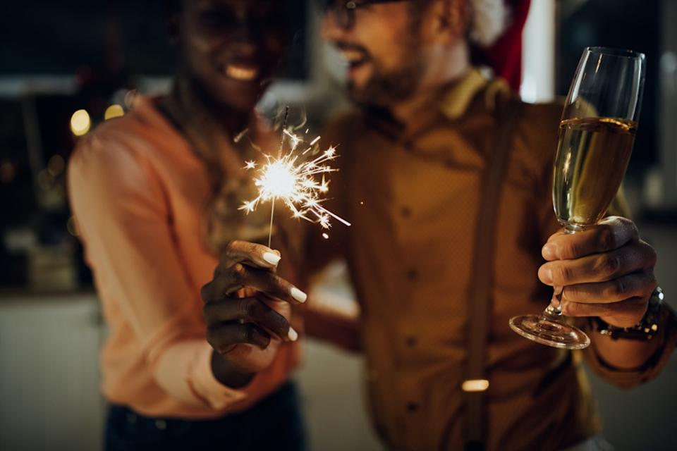 Man and woman holding sparkler and champagne glass on New Year's