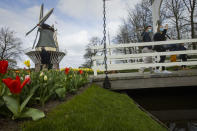 A couple wearing face masks take pictures at the world-famous Keukenhof garden in Lisse, Netherlands, Friday, April 9, 2021. Finally, after month after bleak month of lockdown, there are springtime shoots of hope emerging for a relaxation of coronavirus restrictions at a Dutch flower garden and other public venues. Keukenhof nestled in the pancake flat bulb fields between Amsterdam and The Hague opened its gates Friday to a lucky 5,000 people who were allowed in only if they could show proof on a smartphone app that they had just tested negative for COVID-19. (AP Photo/Peter Dejong)